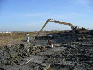 Photo showing contractors digging a channel at Brookhurst Marsh.