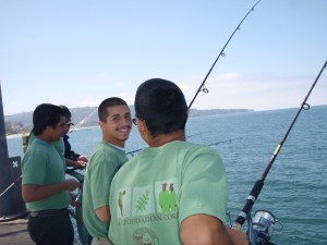 Photo shows young people fishing on Redondo pier.